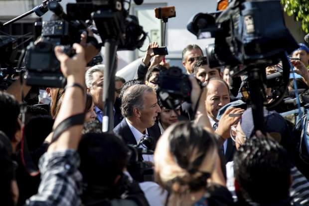 Presidential candidate Jose Antonio Meade is surrounded by the press as he arrives to vote during general elections in Mexico City, Sunday, July 1, 2018. Meade of Mexico's ruling party conceded defeat to Andres Manuel Lopez Obrador in the day's presidential vote. (AP Photo/Anthony Vazquez)