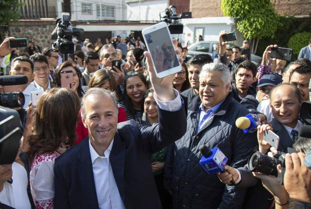 Presidential candidate Jose Antonio Meade, with the Institutional Revolutionary Party (PRI), holds up his cell phone which is connected to a video call with his father who is waving, at a polling station during general elections in Mexico City, Sunday, July 1, 2018. Sunday's elections for posts at every level of government are Mexico's largest ever and have become a referendum on corruption, graft and other tricks used to divert taxpayer money to officials' pockets and empty those of the country's poor. (AP Photo/Anthony Vazquez)