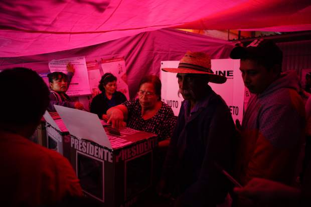 A woman casts her vote inside a polling station covered by a red tarp, during general elections in Iztapalapa, Mexico City, Sunday, July 1, 2018. Sunday's elections for posts at every level of government are Mexico's largest ever and have become a referendum on corruption, graft and other tricks used to divert taxpayer money to officials' pockets and empty those of the country's poor. (AP Photo/Ramon Espinosa)