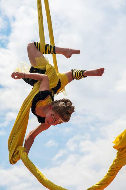 Eight-year-old Peyton Ogren hangs from the aerial silks Queen Bee performance of the Sopris Soarers in the Oasis during the 47th Annual Carbondale Mountain Fair.