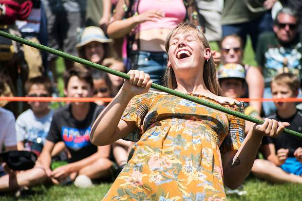 Limbo contestant Tizzy Macgregor grabs the bar after attempting to see how low she can go during the competition on Saturday afternoon at the 47th annual Carbondale Mountain Fair.