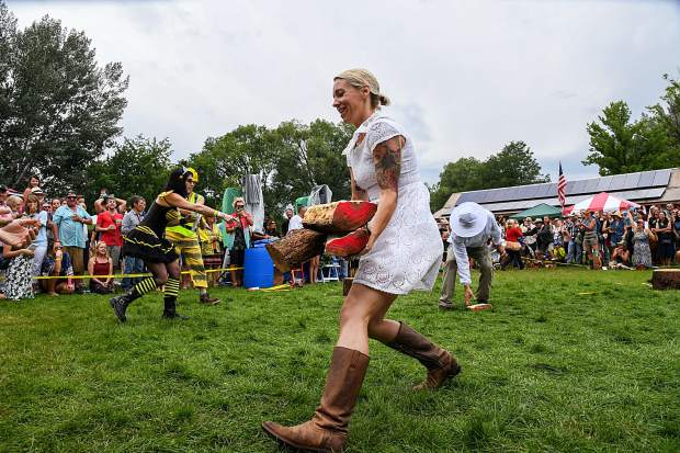 A contestant in the Women's Wood Splitting Contest runs back to the finish line with her chopped pieces in hopes of making the best time during the 47th annual Carbondale Mountain Fair on Saturday afternoon.