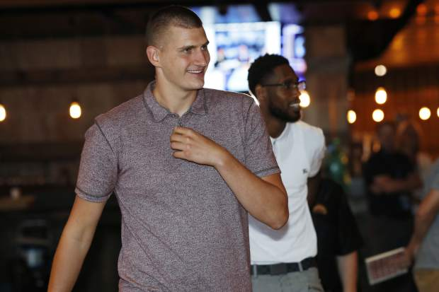 Denver Nuggets center Nikola Jokic, of Serbia, front, and guard Will Barton smile as they enter a news conference to outline a contract extension for Jokic and the re-signing of Barton Monday, July 9, 2018, in Denver. (AP Photo/David Zalubowski)