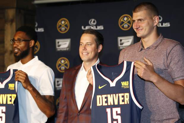 Denver Nuggets center Nikola Jokic, of Serbia, right, joins guard Will Barton, left, and Josh Kroenke, president and governor of the Denver Nuggets, in holding up jerseys during a news conference to outline a contract extension for Jokic and the re-signing of Barton Monday, July 9, 2018, in Denver. (AP Photo/David Zalubowski)