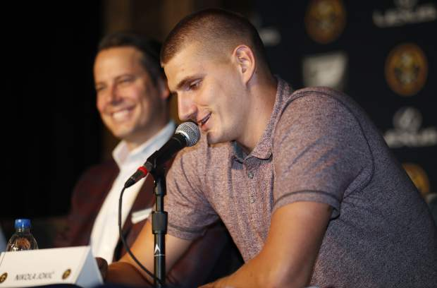 Denver Nuggets center Nikola Jokic, of Serbia, front, jokes with reporters as Josh Kroenke, president and governor of the Denver Nuggets, looks on during a news conference to outline a contract extension for Jokic and the re-signing of guar Will Barton Monday, July 9, 2018, in Denver. (AP Photo/David Zalubowski)