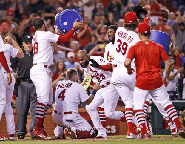 St. Louis Cardinals' Marcell Ozuna (23) is congratulated by teammates after hitting a walk-off home run to defeat the Colorado Rockies 5-4 in a baseball game Monday, July 30, 2018, in St. Louis. (AP Photo/Jeff Roberson)