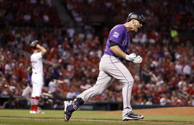 CORRECTS TO RELIEF PITCHER NOT STARTER Colorado Rockies' Nolan Arenado, right, celebrates after hitting a grand slam off St. Louis Cardinals relief pitcher Daniel Poncedeleon, left, during the fifth inning of a baseball game Monday, July 30, 2018, in St. Louis. (AP Photo/Jeff Roberson)