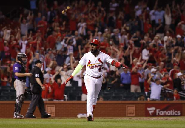 St. Louis Cardinals' Marcell Ozuna tosses his bat in the air after hitting a walk-off home run to defeat the Colorado Rockies 5-4 in a baseball game Monday, July 30, 2018, in St. Louis. (AP Photo/Jeff Roberson)
