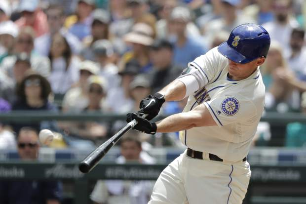 Seattle Mariners' Kyle Seager hits a sacrifice fly to score Dee Gordon during the first inning of a baseball game against the Colorado Rockies, Sunday, July 8, 2018, in Seattle. (AP Photo/Ted S. Warren)