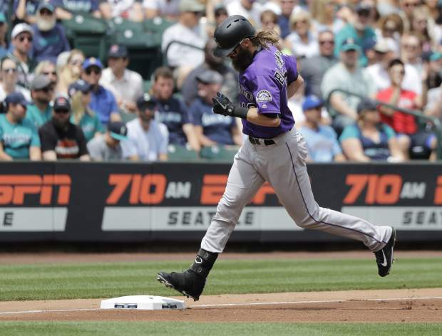 Colorado Rockies' Charlie Blackmon touches third base after he hit a solo home run against the Seattle Mariners during the first inning of a baseball game, Sunday, July 8, 2018, in Seattle. (AP Photo/Ted S. Warren)
