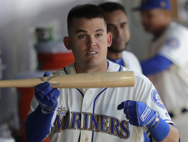 Seattle Mariners' Ryon Healy stands in the dugout and holds a bat belonging to teammate Mitch Haniger after using it to hit a three-run home run against the Colorado Rockies during the sixth inning of a baseball game, Sunday, July 8, 2018, in Seattle. (AP Photo/Ted S. Warren)