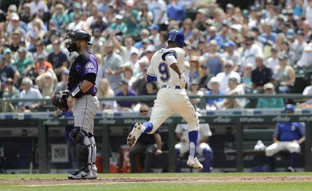 Seattle Mariners' Dee Gordon scores past Colorado Rockies catcher Chris Iannetta on a sacrifice fly hit by Kyle Seager during the first inning of a baseball game, Sunday, July 8, 2018, in Seattle. (AP Photo/Ted S. Warren)