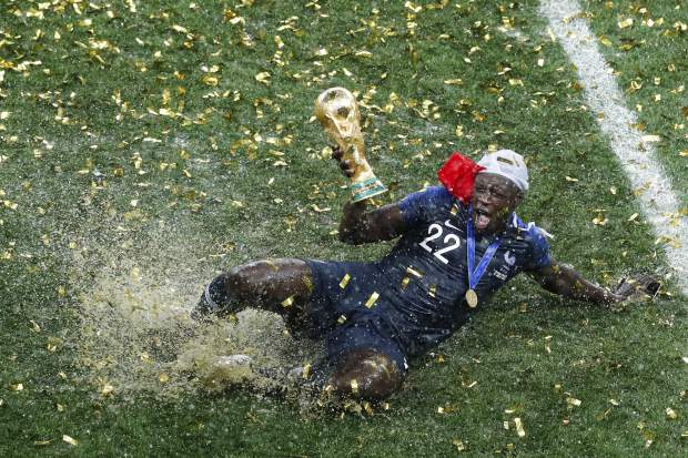 France's Benjamin Mendy celebrates with the trophy after the final match between France and Croatia at the 2018 soccer World Cup in the Luzhniki Stadium in Moscow, Russia, Sunday, July 15, 2018. (AP Photo/Rebecca Blackwell)