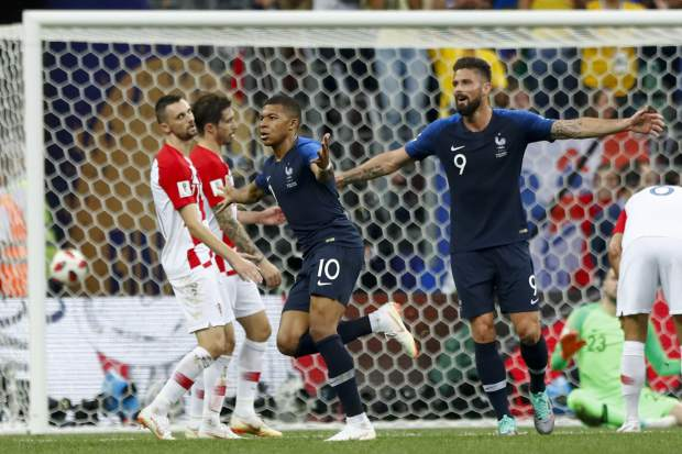 France's Kylian Mbappe,, center, celebrates after scoring his side's fourth goal with teammate France's Olivier Giroud, right, during the final match between France and Croatia at the 2018 soccer World Cup in the Luzhniki Stadium in Moscow, Russia, Sunday, July 15, 2018. (AP Photo/Matthias Schrader)