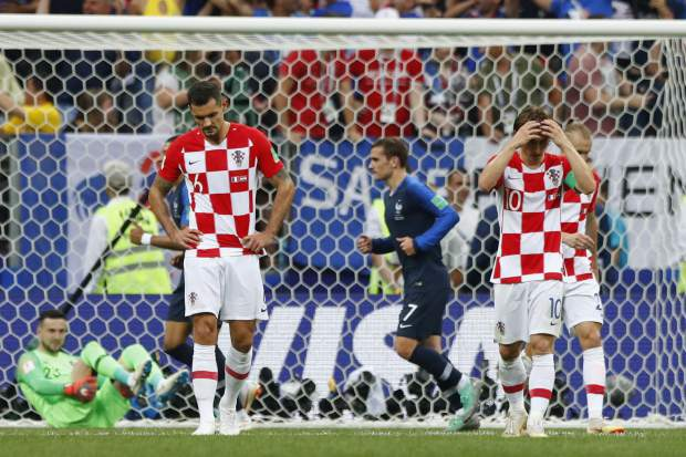 Croatia's Luka Modric, right, and Croatia's Dejan Lovren, left, react after France's Paul Pogba, not in picture, scored his side's third goal during the final match between France and Croatia at the 2018 soccer World Cup in the Luzhniki Stadium in Moscow, Russia, Sunday, July 15, 2018. (AP Photo/Matthias Schrader)