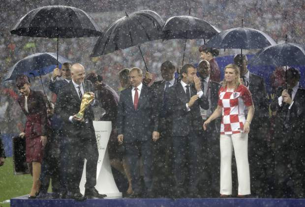 FIFA President Gianni Infantino, Russian President Vladimir Putin, French President Emmanuel Macron and Croatian President Kolinda Grabar-Kitarovic, from left, stand for the presentation in the rain after the final match between France and Croatia at the 2018 soccer World Cup in the Luzhniki Stadium in Moscow, Russia, Sunday, July 15, 2018. France won the final 4-2. (AP Photo/Matthias Schrader)
