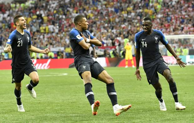 France's Kylian Mbappe, center, celebrates after scoring his side's fourth goal during the final match between France and Croatia at the 2018 soccer World Cup in the Luzhniki Stadium in Moscow, Russia, Sunday, July 15, 2018. (AP Photo/Martin Meissner)