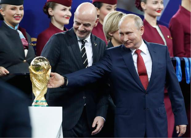 Russian President Vladimir Putin touches the World Cup trophy as FIFA President Gianni Infantino stands beside him, at the end of the final match between France and Croatia at the 2018 soccer World Cup in the Luzhniki Stadium in Moscow, Russia, Sunday, July 15, 2018. France won 4-2. (AP Photo/Petr David Josek)