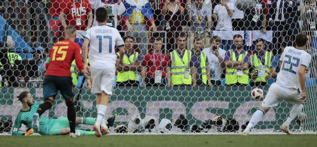 Russia's Artyom Dzyuba, right, runs to celebrate after scoring his side's first goal from a penalty kick past Spain goalkeeper David De Gea, left, during the round of 16 match between Spain and Russia at the 2018 soccer World Cup at the Luzhniki Stadium in Moscow, Russia, Sunday, July 1, 2018. (AP Photo/Alexander Zemlianichenko)