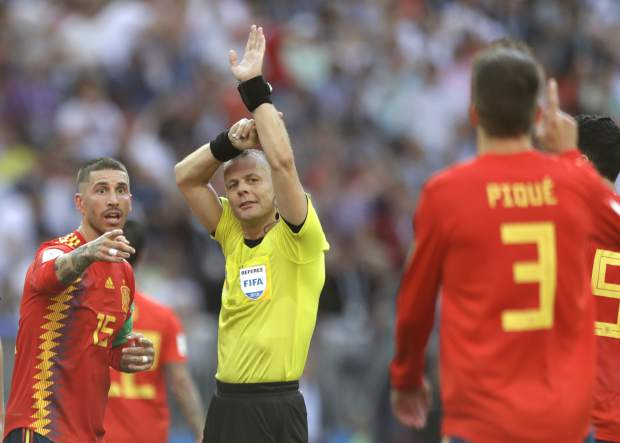 Referee Bjorn Kuipers from Netherlands indicates a handball by Spain's Gerard Pique, front, during the round of 16 match between Spain and Russia at the 2018 soccer World Cup at the Luzhniki Stadium in Moscow, Russia, Sunday, July 1, 2018. (AP Photo/Matthias Schrader)