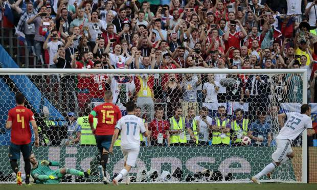 Russia's Artyom Dzyuba, right, runs to celebrate scores his side's first goal from a penalty kick past Spain goalkeeper David De Gea, 2nd left, during the round of 16 match between Spain and Russia at the 2018 soccer World Cup at the Luzhniki Stadium in Moscow, Russia, Sunday, July 1, 2018. (AP Photo/Alexander Zemlianichenko)