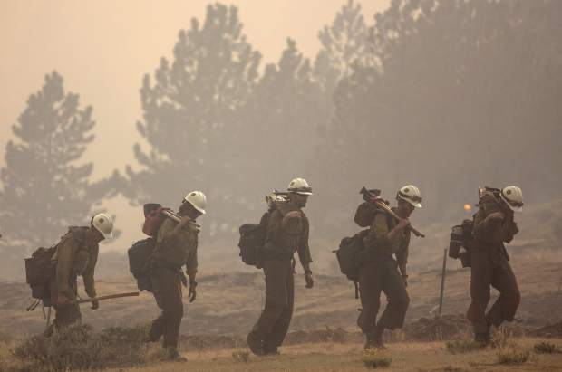 Members of the Craig Hotshots firefighters return from battling the Weston Pass Fire, Monday, July 2, 2018, near Fairplay, Colo. In Colorado, more than 2,500 homes were under evacuation orders as firefighters battled more than a half-dozen wildfires. (Hugh Carey/Summit Daily News via AP)