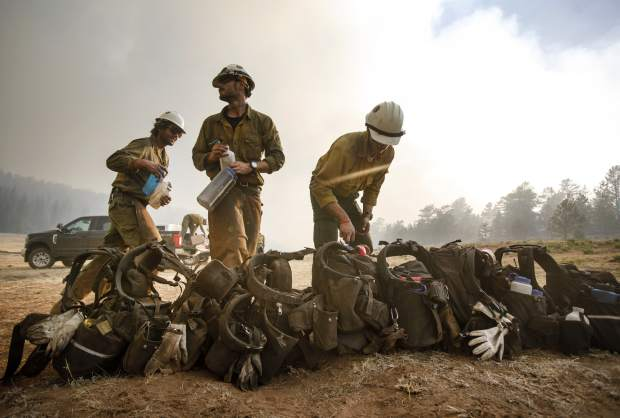 Craig Hotshots firefighters take a break from battling the Weston Pass Fire, Monday, July 2, 2018, near Fairplay. In Colorado, more than 2,500 homes were under evacuation orders as firefighters battled more than a half-dozen wildfires. (Hugh Carey/Summit Daily News via AP)