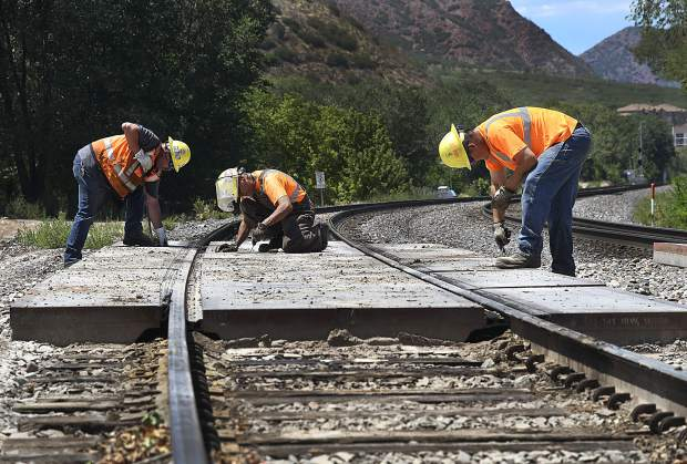 The early afternoon sun beats down on, from left, Jeff Skinner, Adam Diaz and Mario Lara, all with Union Pacific Railroad, as they clean the rock and debris from crossing panels on the railroad tracks west of the new Grand Avenue Bridge Monday in Glenwood Springs. The crew based out of Grand Junction was working to remove the panels that had been used by construction vehicles to access the north side of the tracks during bridge construction.