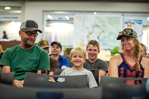 Colby Samuelson, 8, center, flashes a giant grin after publicly announcing at the community meeting,