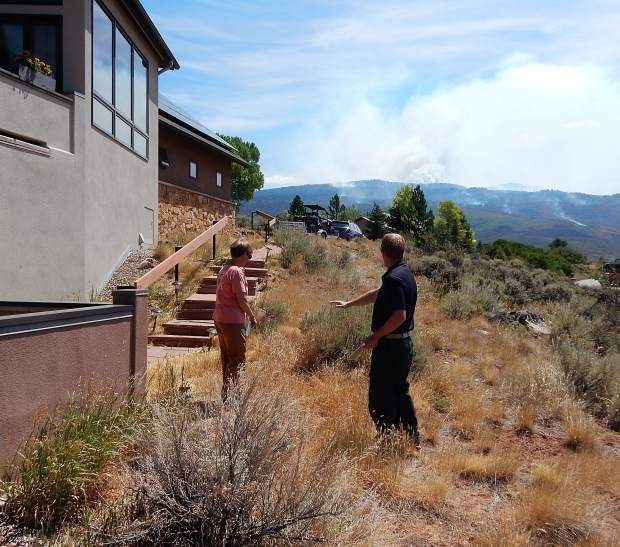 Eagle County Wildfire Mitigation Coordinator Eric Lovgren, right, consults with Nancy Bobrow Julu 19 about mitigation of her property in Missouri Heights. The Lake Christine Fire burns in the background.