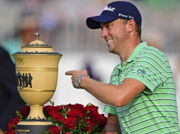 Justin Thomas points the Gary Player Cup trophy after winning the final round of the Bridgestone Invitational golf tournament at Firestone Country Club, Sunday, Aug. 5, 2018, in Akron, Ohio. (AP Photo/David Dermer)
