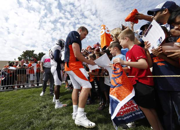 Denver Broncos quarterback Case Keenum, front, and linebacker Von Miller give autographs to fans after an NFL football training camp Sunday, Aug. 5, 2018, in Englewood, Colo. (AP Photo/David Zalubowski)