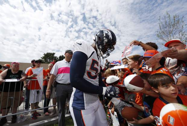 Denver Broncos linebacker Von Miller gives autographs to fans after an NFL football training camp Sunday, Aug. 5, 2018, in Englewood, Colo. (AP Photo/David Zalubowski)