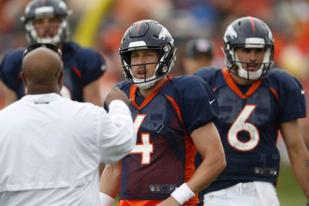 Denver Broncos running backs coach Curtis Bodkins, front, directs quarterbacks Case Keenum, center, and Paxton Lynch, back left, and Chad Kelly during drills at the team's headquarters during an NFL football training camp Sunday, Aug. 5, 2018, in Englewood, Colo. (AP Photo/David Zalubowski)