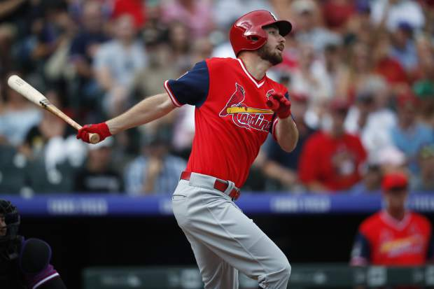 St. Louis Cardinals' Austin Gomber hits an infield single to drive in two runners off Colorado Rockies starting pitcher Tyler Anderson in the first inning of a baseball game Sunday, Aug. 26, 2018, in Denver. (AP Photo/David Zalubowski)