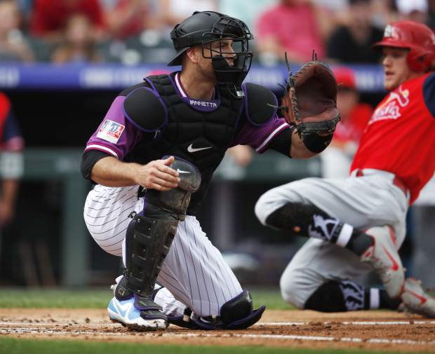 Colorado Rockies catcher Chris Iannetta, front, waits for the throw as St. Louis Cardinals' Harrison Bader scores from second base on an infield single hit by Austin Gomber in the first inning of a baseball game Sunday, Aug. 26, 2018, in Denver. (AP Photo/David Zalubowski)