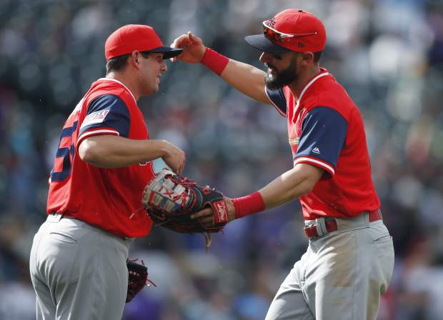 St. Louis Cardinals first baseman Matt Carpenter, right, congratulates relief pitcher Dominic Leone after the ninth inning of a baseball game against Colorado Rockies, Sunday, Aug. 26, 2018, in Denver. (AP Photo/David Zalubowski)