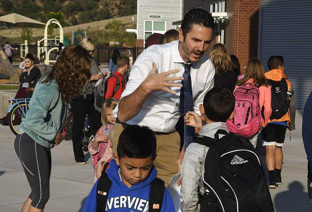 Riverview Principal Adam Volek gives a student a special handshake as he meets students when they arrive Monday at Riverview School.