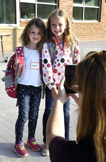 Stephanie Averill stops to get a first day of school picture of her daughters Logan 4, left, and Amelia, 6 as her and her husband Zachery Averill drop them off for th first day of school Monday.