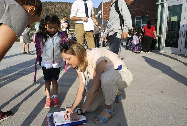 A staff member helps a new student check in during the first day of school Monday at Riverview School in Glenwood Springs.