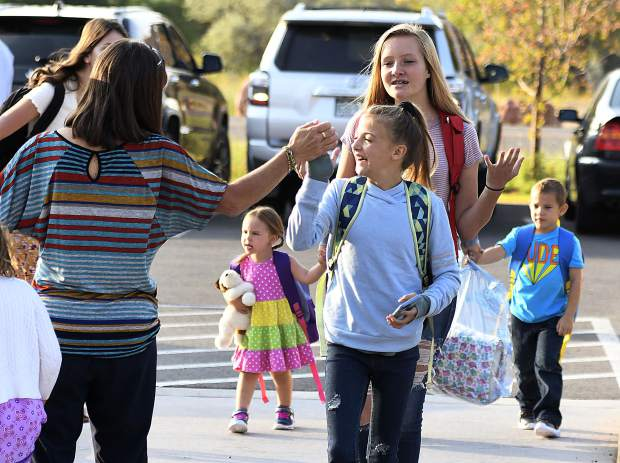 A students gets a high five from the crossing guard Monday at Riverview School in Glenwood Springs.
