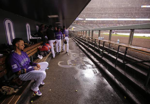 Colorado Rockies' Carlos Gonzalez sits in the dugout during a rain delay in the fifth inning of a baseball game against the Pittsburgh Pirates, Monday, Aug. 6, 2018, in Denver. (AP Photo/Jack Dempsey)