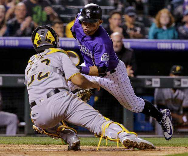 Pittsburgh Pirates catcher Elias Diaz (32) tags out Colorado Rockies' Gerardo Parra during the fifth inning of a baseball game, Monday, Aug. 6, 2018, in Denver. (AP Photo/Jack Dempsey)
