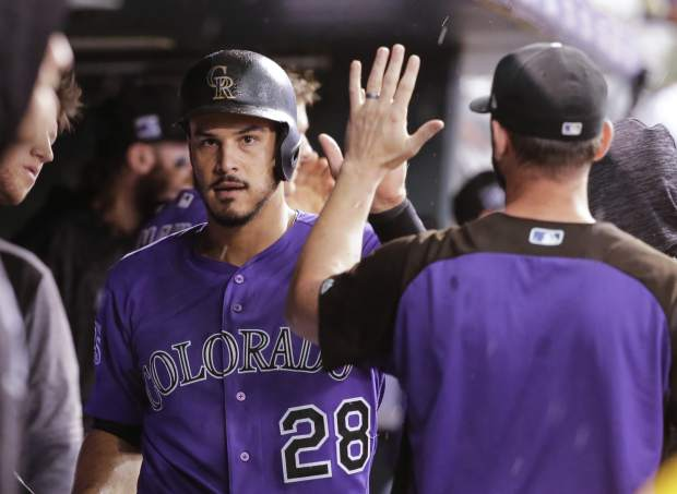 Colorado Rockies' Nolan Arenado is congratulated by teammates in the dugout after scoring on a Gerardo Parra force attempt during the fifth inning of a baseball game against the Pittsburgh Pirates, Monday, Aug. 6, 2018, in Denver. (AP Photo/Jack Dempsey)