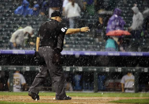 Home plate umpire Eric Cooper calls everyone in for a rain delay during the fifth inning of a baseball game between the Colorado Rockies and the Pittsburgh Pirates, Monday, Aug. 6, 2018, in Denver. (AP Photo/Jack Dempsey)