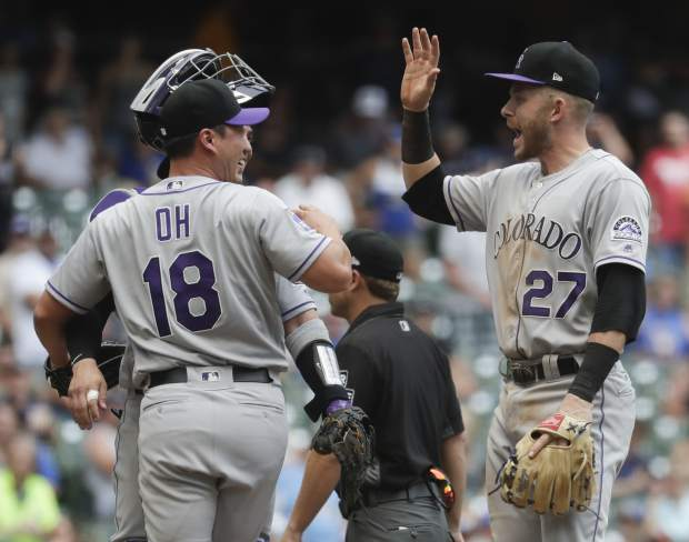 Colorado Rockies' Seunghwan Oh (18) and Trevor Story celebrate after the 11th inning of a baseball game against the Milwaukee Brewers Sunday, Aug. 5, 2018, in Milwaukee. The Rockies won 5-4. (AP Photo/Morry Gash)