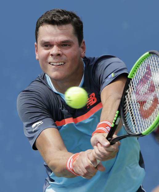 Milos Raonic, of Canada, returns a shot to Carlos Berlocq, of Argentina, during the first round of the U.S. Open tennis tournament, Monday, Aug. 27, 2018, in New York. (AP Photo/Jason DeCrow)