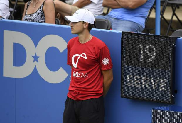 In this Friday, Aug. 3, 2018, photo, a ball boy stands next to the serve clock during a match between Kei Nishikori, of Japan, and Alexander Zverev, of Germany, at the Citi Open tennis tournament in Washington. (AP Photo/Nick Wass)