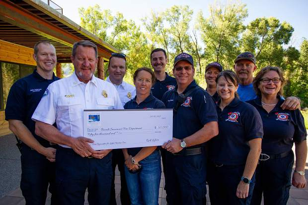 Basalt-Snowmass Village firefighters display the replica check for $55,000 the department received Thursday from the Roaring Fork Conservancy.