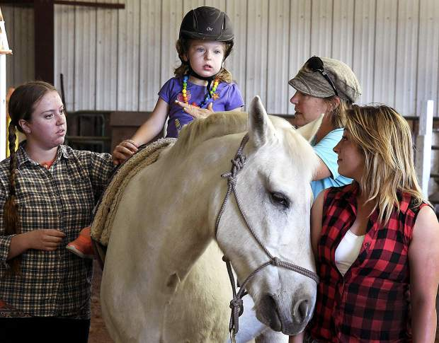 WindWalkers staff work with Grace McGlade, 3, of New Castle during a therapy session at the Missouri Heights-based equine-assisted learning and therapy center. The nonprofit is where horses and professionals help indviduals and families with challenges from Aspen to Rifle. See Friday's Post Independent for more of WindWalkers.